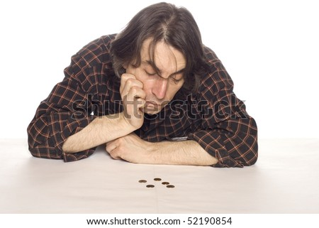 The man looks at coins in meditation. - stock photo