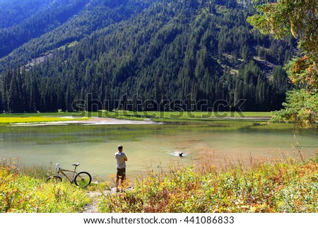 The man looks how his dog swims to shore. Cyclist. Beautiful mountains landscape - stock photo