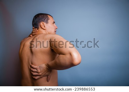 the man of European appearance brunet holding hands behind his back feels pain in the back - stock photo