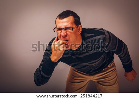 the man of European appearance brunet in a sweater put his fingers in his mouth on a gray background, nausea, vomiting retro - stock photo
