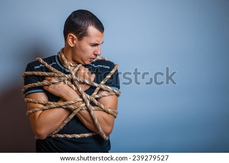 the man of European appearance brunet tied with rope on a gray background - stock photo