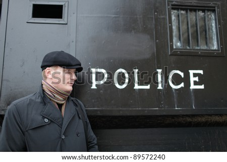 The man posing on the police carriage background - stock photo