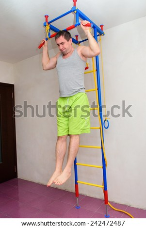 The man pulled on the wall bars - stock photo