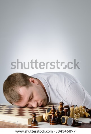 The man put his head on a chess board, and closed his eyes - stock photo