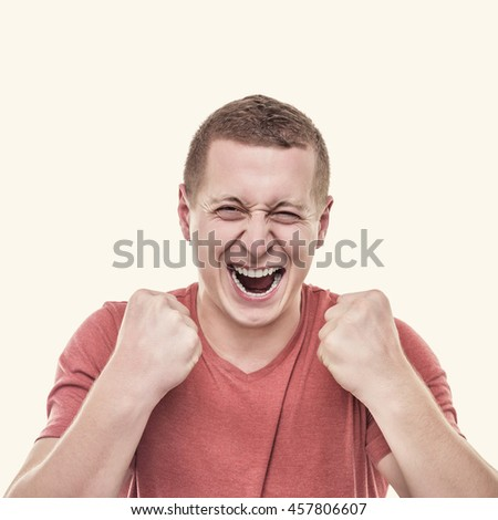 The man rejoices victory holding up fists. Toned photo. - stock photo