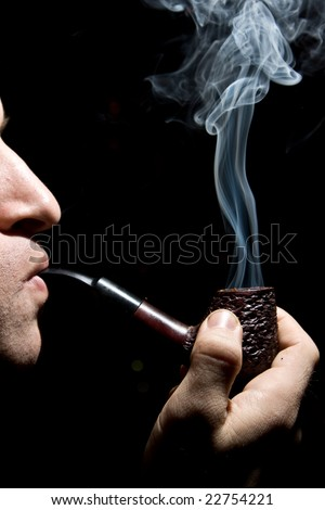 The man smoking tobacco pipe on black background - stock photo