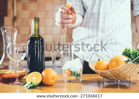 The man squeezes grapefruit juice in a decanter for making home sangria for home party, home kitchen interior. - stock photo