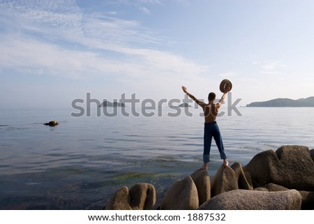 The man stands on rocks and holds hat.Coast.Evening.Sunset. - stock photo