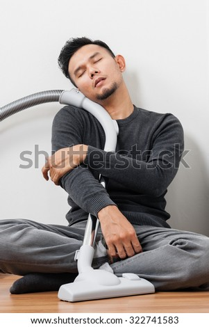The man take a nap after cleaning home with vacuum cleaner - stock photo