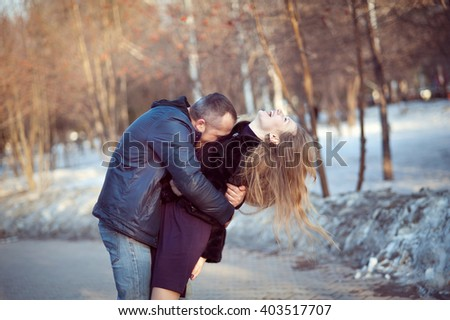 The man tightly hugs the woman, she laughs, tilting his head back, spring, Park. - stock photo