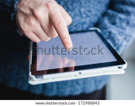 The man uses a tablet PC. Modern gadget in hand. - stock photo