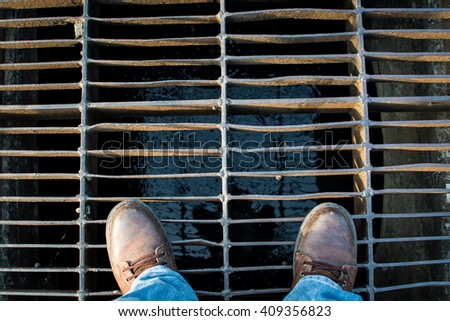The man wear boots stand on Sewer cover or storm drain in stree - stock photo