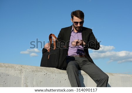 The man with a bag is sitting on a concrete block and looking at his watch - stock photo