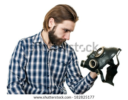 the man with beard watching at a gas mask - stock photo