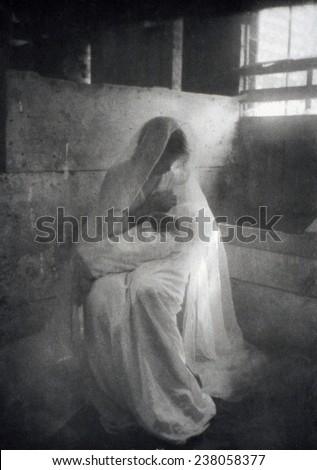 The Manger, by Gertrude Kasebier, shows a woman as the Virgin Mary posed as though breast feeding the baby Jesus, ca 1900. - stock photo