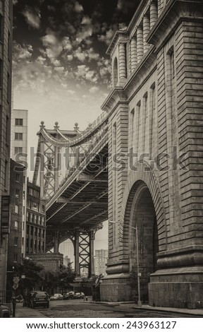 The Manhattan Bridge between buildings, Brooklyn. Street view at sunset. - stock photo