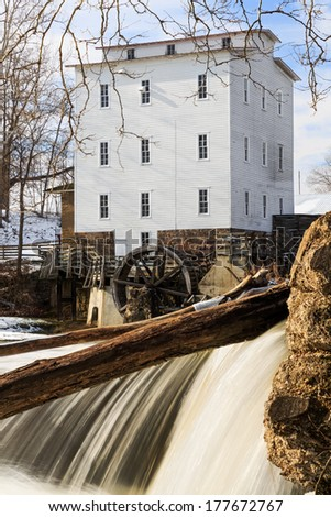The Mansfield Roller Mill, a grist mill powered by the flowing waters of Indiana's Big Raccoon Creek, was built in 1820 and is on the US Register of Historic Places. - stock photo