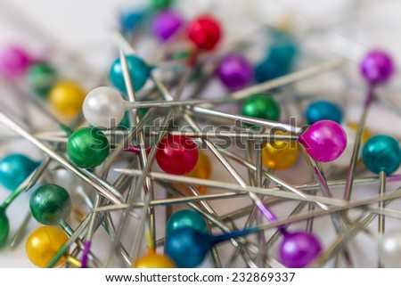 the many sewing push pins together on the white background - stock photo