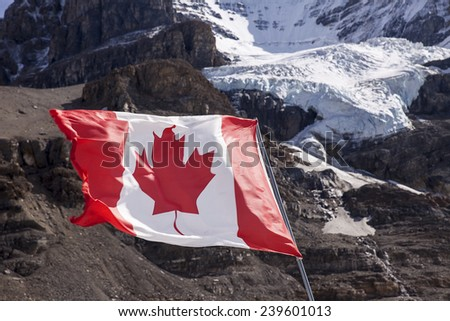 The maple leaf of the Canadian Flag flutters in a brisk wind. In the background, the main glacier of Mount Andromeda tumbles from the summit headwall. - stock photo