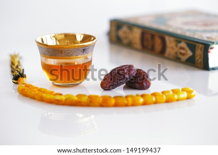 The Masbaha is also known as Tasbih photographed here with the Quran, Arabic Tea and dried dates - all symbols of Ramadan - stock photo