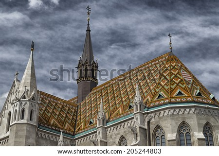 The Mathias Church in Budapest (Hungary) or Church of Our Lady: red and orange diamond patterned roof tiles, neo-Gothic rose window and white towers on deep dramatic dark cloudy sky - stock photo