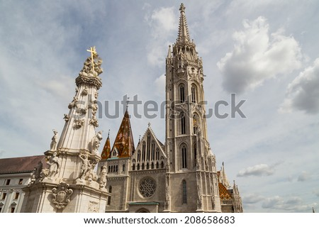 The Mathias Church in Budapest (Hungary) or Church of Our Lady: red and orange diamond patterned roof tiles, neo-Gothic rose window and white towers on cloudy but sunny sky - stock photo
