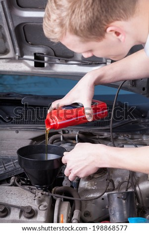 The mechanic completes the engine oil level - stock photo