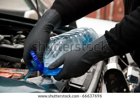 The mechanic fills washing liquid to the car - stock photo