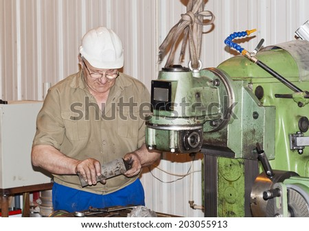 The mechanic operates the production equipment - stock photo