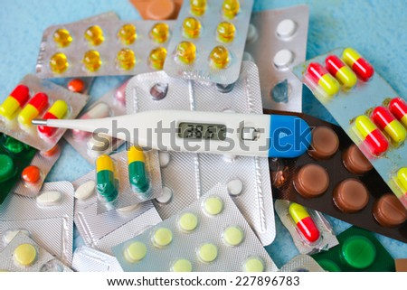 The medical thermometer 38,5 and medicines in tablets - stock photo
