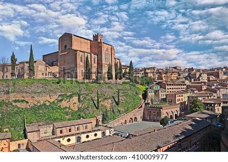 The medieval church Basilica of San Domenico on the hill above source Fontebranda in the ancient town Siena in Tuscany, Italy - stock photo