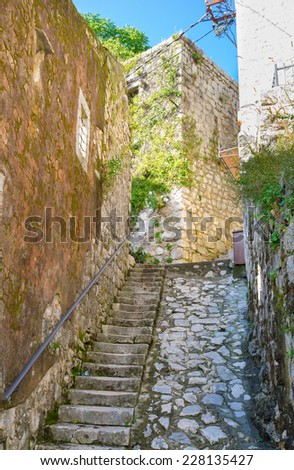 The medieval streets of Perast are made of white stone, Montenegro. - stock photo