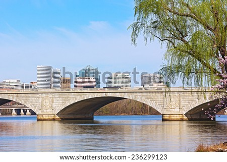The Memorial Bridge over Potomac River and a city skyline during cherry blossom in Washington DC. Cherry trees bloom on a bank of Potomac River in Washington DC. - stock photo