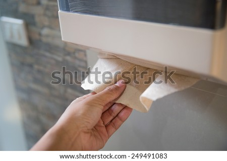 The men were picked up toilet paper in the bathroom. - stock photo