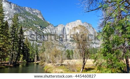 The Merced River in Yosemite Valley in Yosemite National Park in California, striking rocks of the Sierra Nevada with Yosemite Falls, landscape in autumn, blue sky/In Yosemite Valley in United States - stock photo