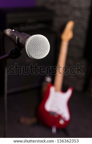 The microphone at the front with a fuzzy guitar in the background - stock photo