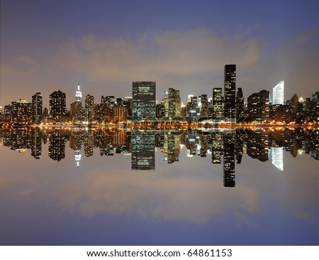 The midtown Manhattan Skyline across from the UN with serious reflections in New York City. - stock photo