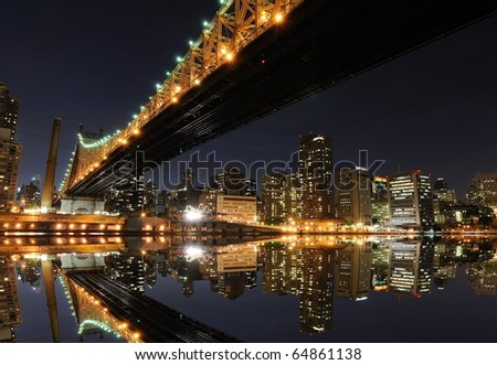 The midtown Manhattan Skyline with serious reflections in New York City under the Queensboro Bridge. - stock photo