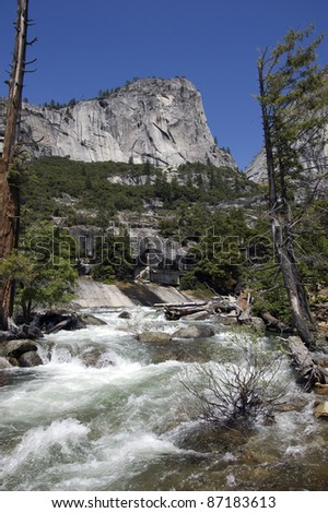 The Mighty Merced: The Merced River upstream of the world famous Vernal Falls in Yosemite National Park. Majestic Mount Broderick keeps watch over the river which is flanked by weathered pine trees. - stock photo