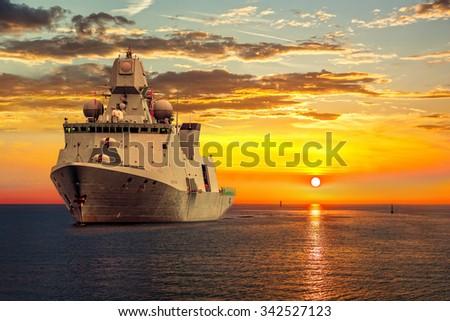 The military ship on sea at sunrise.  - stock photo