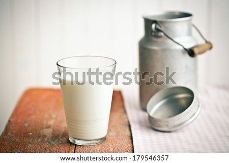 the milk in glass on old wooden table - stock photo