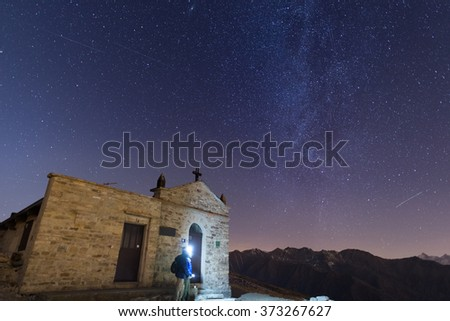 The Milky Way and the starry sky from high up on the Alps with scenic mountain landscape. People standing aside a little chapel with lightning gear on. - stock photo