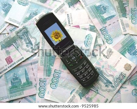 The mobile phone laying on banknotes of Russia - stock photo