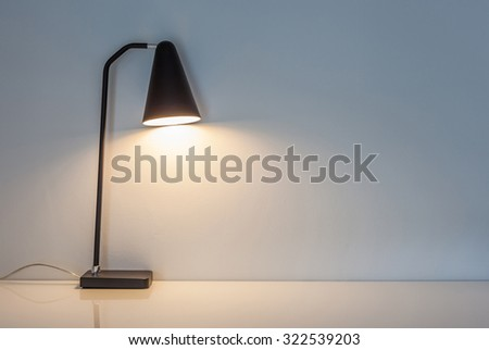 The modern desk lamp illuminate on the wall background. (left the right space for text) - stock photo