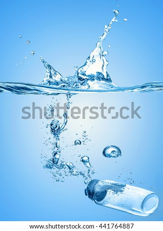 The moisturizing shampoo, cosmetic liquid, tonic falls into the blue water with big water splash on the gradient blue water background and many blue air bubbles   - stock photo