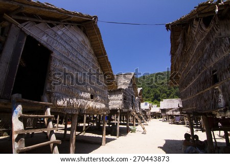 The Moken Sea Gypsy Village at Koh Surin Tai in the Mu Ko National Park, Surin Islands of Thailand with its thatched houses on stilts. - stock photo