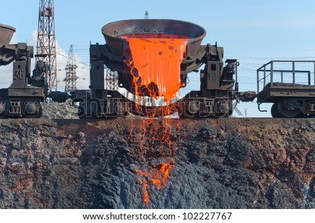 The molten steel is poured into the slag dump. The molten slag is poured from a bucket mounted on a railway platform. - stock photo