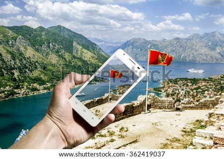 The Montenegro flag on the fortress of Kotor in the lens of the smartphone camera.Montenegro - stock photo