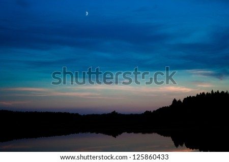 the moon in the late evening sky over the lake - stock photo