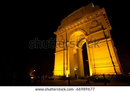 The moon is visible through Delhi's India Gate memorial, tastefully illuminated by floodlights at night - stock photo